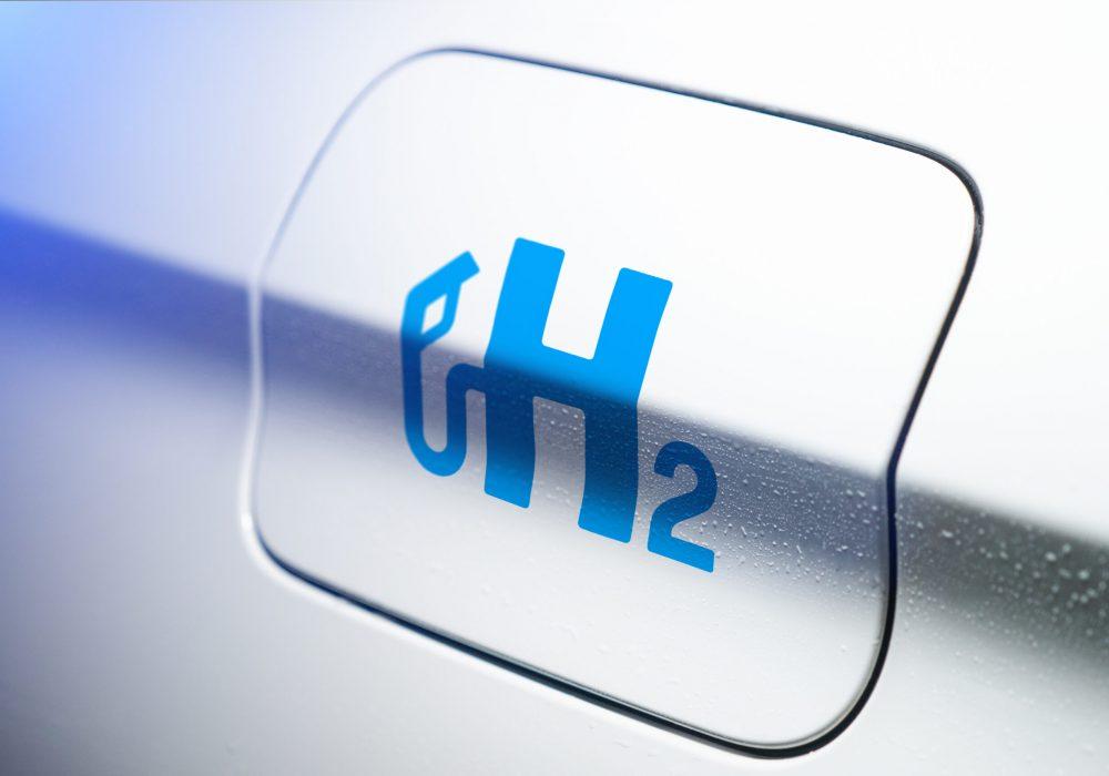Car with hydrogen logo on filler cap. h2 combustion engine for emission free ecofriendly transport.
